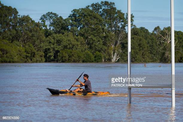 A resident uses a kayak to paddle past goal posts partially submerged under floodwaters caused by Cyclone Debbie to rescue a stranded cow on his...