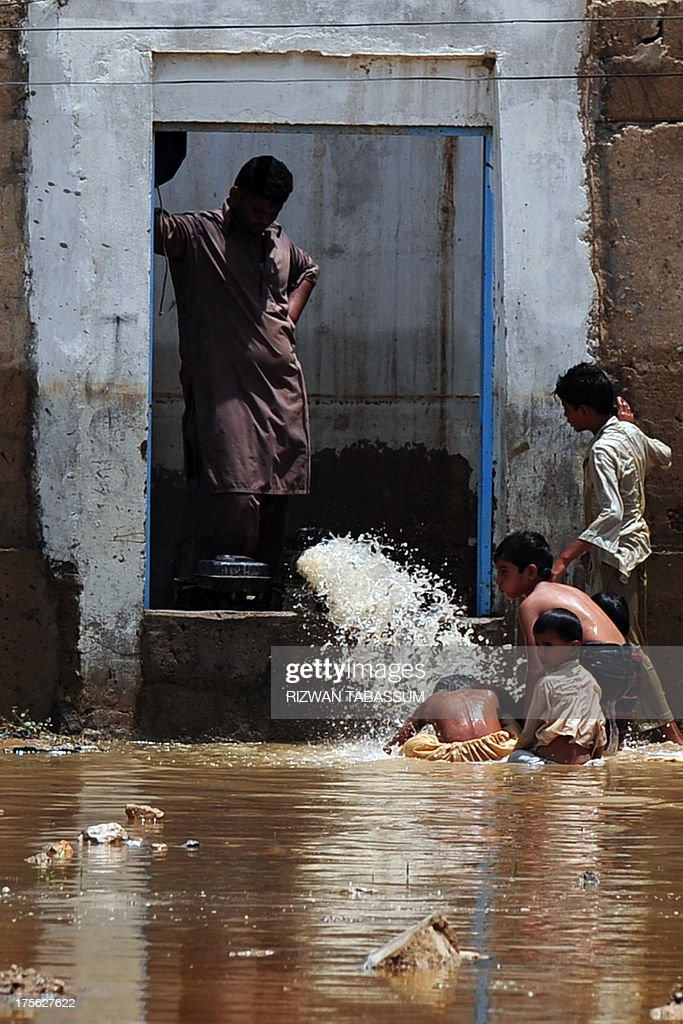 A resident uses a pump to remove water from his home as children play in floodwaters in the aftermath of floods at a residential area of Karachi on August 5, 2013. Pakistani disaster relief officials issued fresh flood warnings after the death toll from heavy monsoon rains rose to 45 and waters paralysed parts of the largest city Karachi. Flash floods caused by monsoon downpours have inundated some main roads in the sprawling port city and swept away homes in the northwestern province of Khyber Pakhtunkhwa.