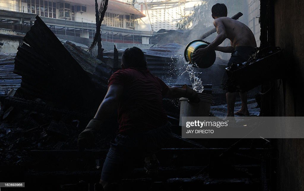 A resident uses water to douse a fire that engulfed shanty homes in Manila on March 1, 2013 where a child died during the fire and a fireman was injured according to fire investigators. The Bureau of Fire and Protection encourage everyone to join in the observance of the 47th Fire Prevention Month during a kick-off ceremony at Quezon Memorial Circle. AFP PHOTO / Jay DIRECTO.