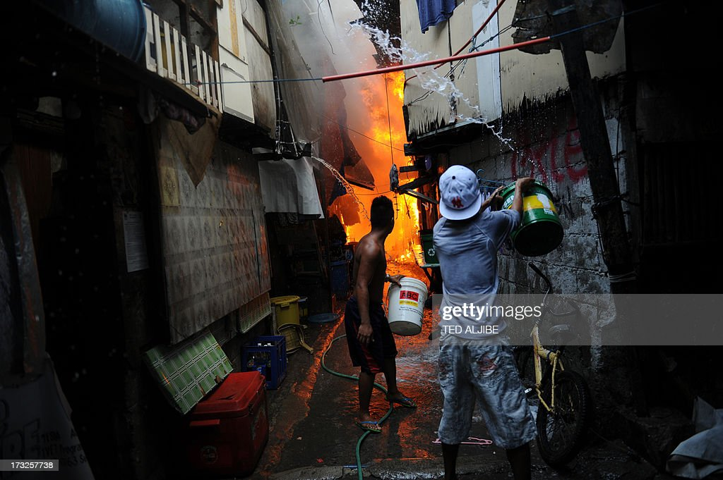 A resident using a bucket to put out a fire after a fire engulfed a shanty town at the financial district of Manila on July 11, 2013. There were no immediate reports of casualties from the blaze, which occurred mid-morning amid government plans to relocate thousands of families living in areas vulnerable to floods and typhoons.