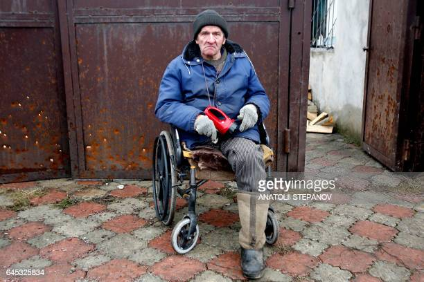 TOPSHOT Resident Viktor Gudelya who lost a leg during a 2014 shelling watches firemen extinguishing a fire in his house in Avdiivka destroyed as a...