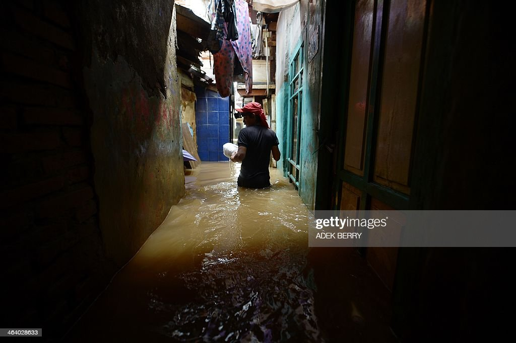 A resident wades through a flooded neighbourhoud in Jakarta on January 20, 2014. More than 30,000 Indonesians have fled their homes in the capital due to flooding that has left five dead, officials said January 19, with people using rubber dinghies and wading through waist-deep water to reach safer ground.
