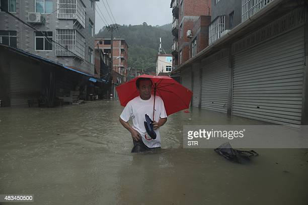 A resident wades through a flooded street as Typhoon Soudelor brought heavy rain to Ningde eastern China's Fujian province on August 9 2015 A...