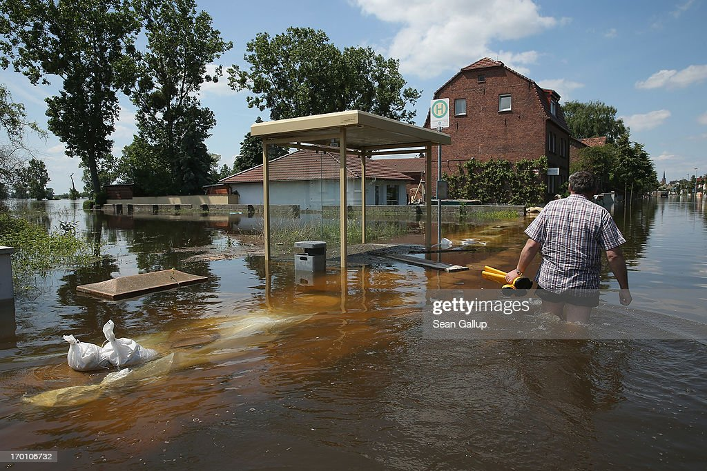 A resident wades through a flooded street next to a bus stop near the swollen Elbe river on June 7, 2013 in Elster, Germany. Floodwaters that have devastated parts of Saxony and Thuringia are now moving north, threatening towns along the Elbe and Saale rivers all the way to Hamburg. Eastern and southern Germany are suffering under floods that in some cases are the worst in 400 years. At least four people are dead and tens of thousands have evacuated their homes.