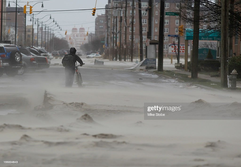 A resident walks down a street covered in beach sand due to flooding from Hurricane Sandy on October 30 2012 in Long Beach New York The storm has...