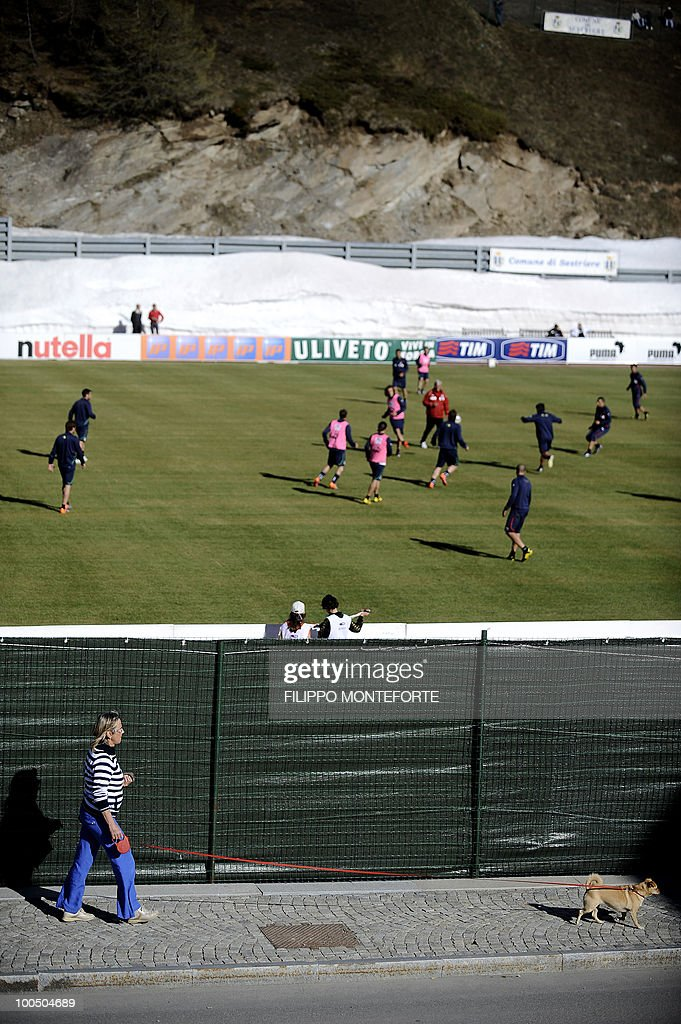 A resident walks her dog during Italy's soccer team training session in Sestriere on May 25, 2010. The Italian team started today a retreat in the mountains of Sestriere before the FIFA World Cup 2010 in South Africa .AFP PHOTO / Filippo MONTEFORTE