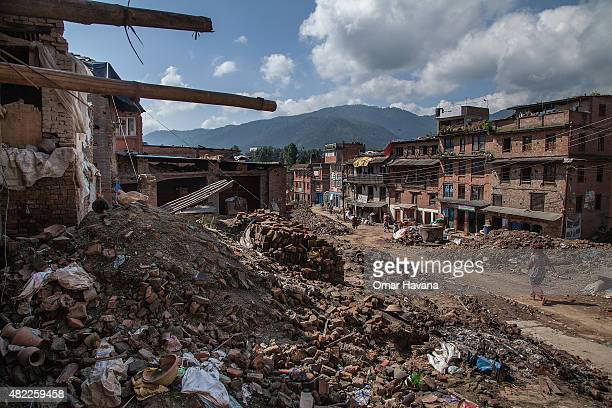 A resident walks in a street covered by debris from collapsed and damaged homes on July 29 2015 in Bhaktapur Nepal Three months after the earthquake...