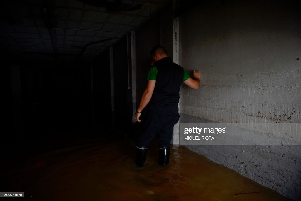 A resident walks into a flooded garage after heavy rains in the village of Redondela, northwestern Spain, on February 13, 2016. / AFP / AFP or licensors / MIGUEL RIOPA