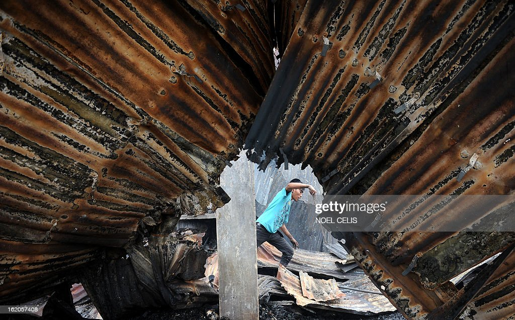 A resident walks over debris of destroyed houses near a collapsed roof after an overnight fire in a slum area in Manila on February 19, 2013. Almost 500 houses were destroyed, leaving 2,000 residents homeless according to a local media report.