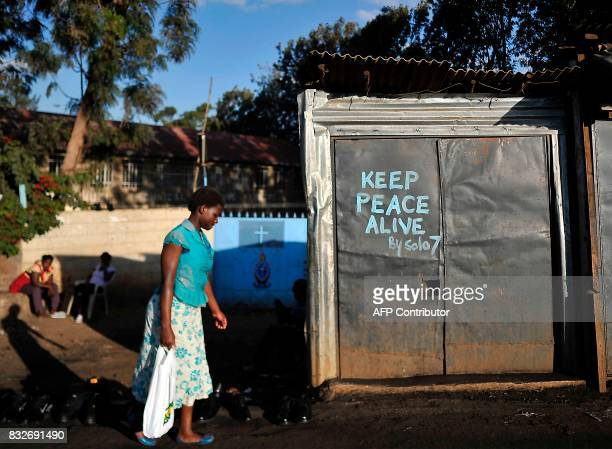 TOPSHOT A resident walks past a closed shop with a message calling for peace painted on its doors in the Kibera district of Nairobi on August 16 as...