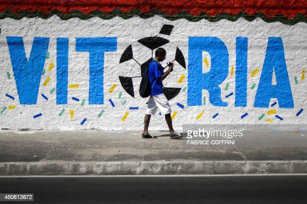 A resident walks past a decorated wall next to The Arena Amazonia in Manaus on June 14 ahead of the England v Italy match of the 2014 FIFA World Cup...