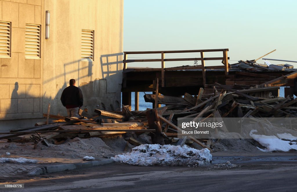 A resident walks past a destroyed section of the boardwalk at the base of Lincoln Boulevard as Long Islanders continue their clean up efforts in the aftermath of Superstorm Sandy on November 9, 2012 in Long Beach, New York. New York Gov. Andrew M. Cuomo has said that the economic loss and damage to homes and business caused by Sandy could total $33 billion in New York, according to published reports.