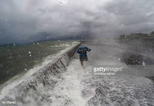 TOPSHOT A resident walks past big waves spilling over a wall onto a coastal road in the city of Legaspi in Albay province south of Manila on December...
