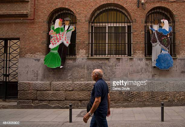 A resident walks past caricatures representing traditional 'chulapos' dancing the authentic 'chotis' dance in the historic La Latina neighbourhood...