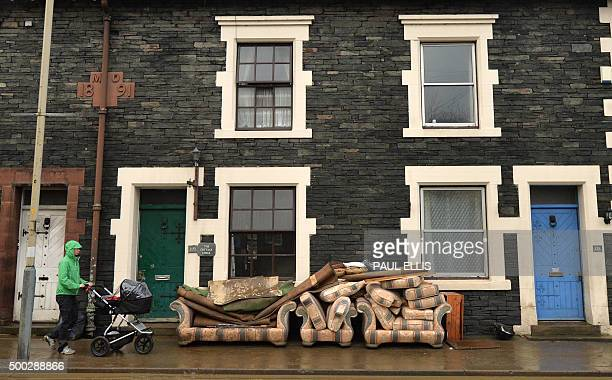 TOPSHOT A resident walks past furniture placed outside a house in Keswick northern England on December 7 2015 following heavy flooding in the town...