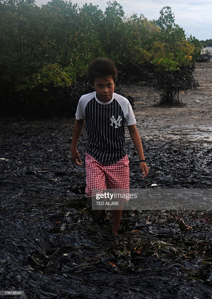 A resident walks through a mangrove area affected by an oil slick near the site of a ferry and freighter collision in Cordova town near Cebu City, central Philippines on August 18, 2013. Philippine divers hauled bodies out of rough seas August 18 in the grisly aftermath of a ferry disaster that claimed at least 38 lives, as oil leaked from the vessel, spreads for more than five kilometres (three miles) and into coastal villages, fishing grounds and mangroves. AFP PHOTO/TED ALJIBE
