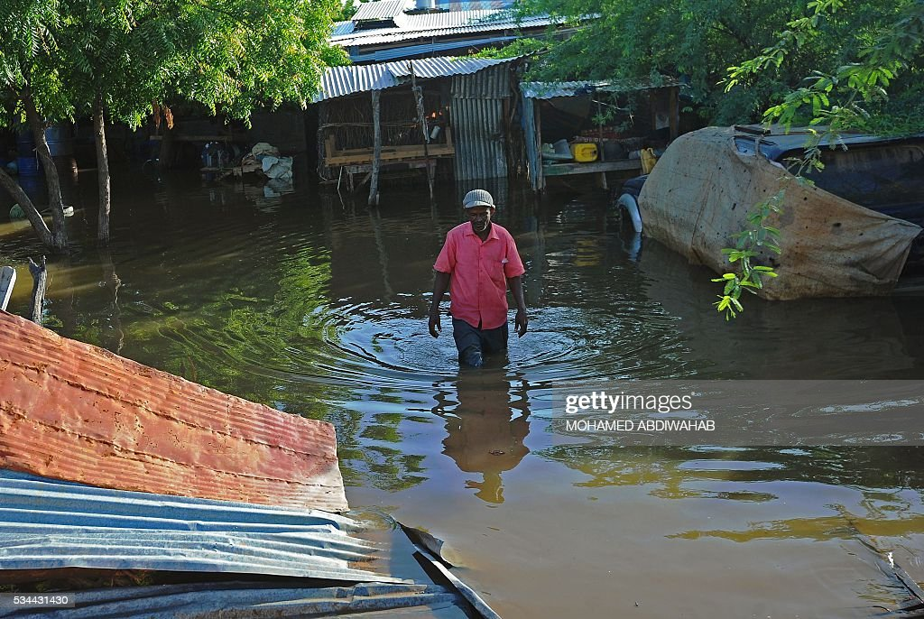 A resident walks through flooded streets in Beledweyne, north of Mogadishu on May 26, 2016. Hundreds of families have been forced out of their homes following flash floods in Beledweyne after torrential rains pounded the area in the last few days.The heavy rains led to the bursting of River Shabelle which caused massive floods in residential areas along the river. / AFP / MOHAMED