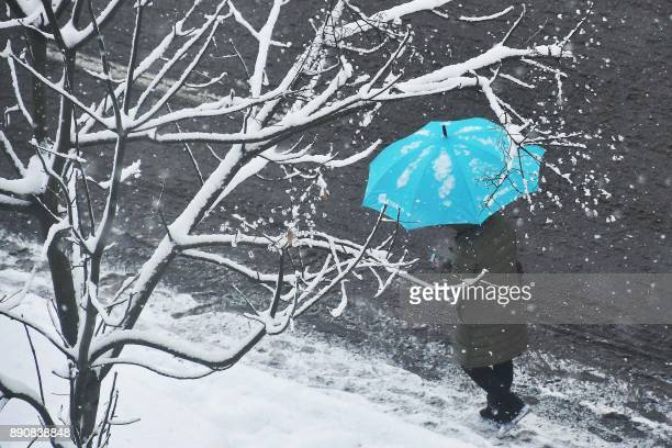 A resident walks with an umbrella during snowfall in Yantai in China's eastern Shandong province on December 12 2017 A blue alert for a snowstorm and...