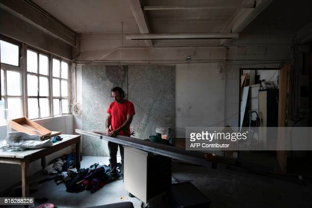 A resident works on July 15 2017 in an apartment of the Cite de Jarry a former industrial building in Vincennes converted into an artistic squat and...