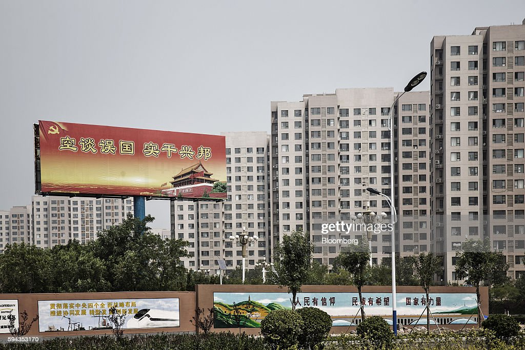 Residential and commercial buildings stand near a banner at the Caofeidian industrial zone near Tangshan Hebei province China on Wednesday Aug 10...