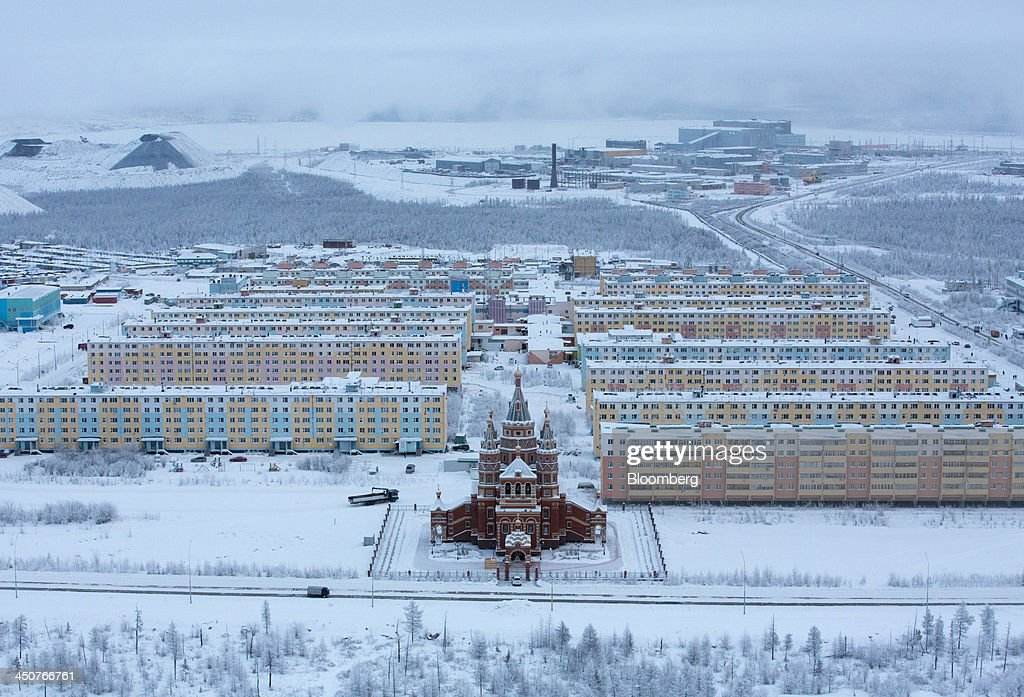 Residential apartment blocks for workers stand beyond a Russian orthodox church near the Udachny diamond mine operated by OAO Alrosa in Udachny, Russia, on Saturday, Nov. 16, 2013. OAO Alrosa, the world's largest diamond producer, raised about $1.3 billion in an oversubscribed share sale from investors including Oppenheimer Funds Inc. and Lazard Ltd.'s asset-management unit, First Deputy Prime Minister Igor Shuvalov said. Photographer: Andrey Rudakov/Bloomberg via Getty Images