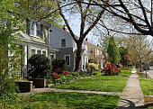 Early spring neighborhood in Richmond, Virginia-refurbished homes, trees, plants, flowers, lawns and sidewalk. Horizontal.