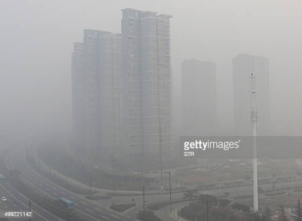 Residential blocks are seen covered in smog in Lianyungang eastern China's Jiangsu province on November 30 2015 Beijing choked under the worst smog...