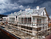 Residential building final works on facade, scaffold, modern architecture, wooden fence, heavy clouds