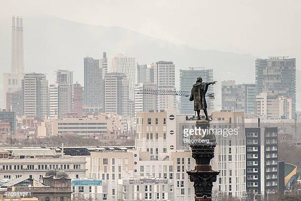 Residential buildings and skyscrapers stand beyond a statue on the city skyline in Barcelona Spain on Friday Feb 21 2014 A smart city initiative...