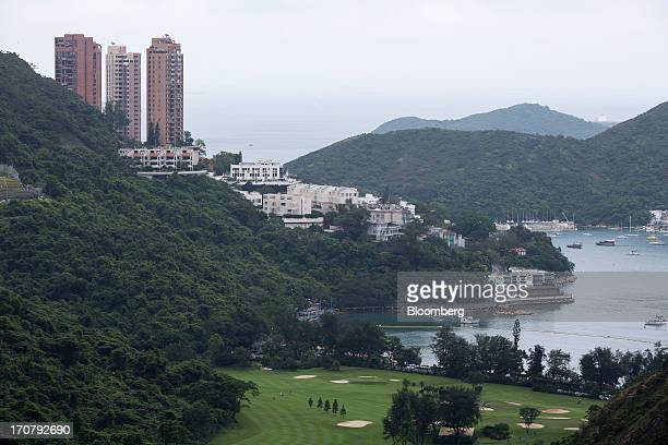 Residential buildings look over the Hong Kong Golf Club golf course foreground in the Deep Water Bay area of Hong Kong China on Sunday June 16 2013 A...