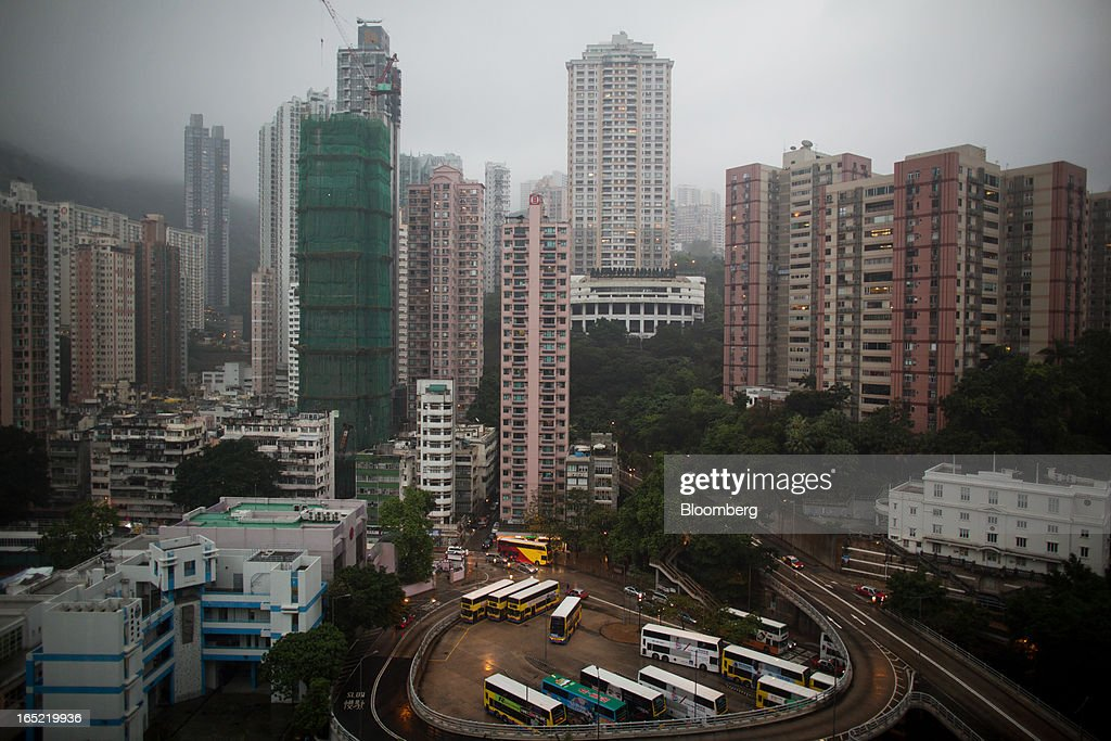 Residential buildings stand behind a bus depot in the Tai Hang area of Hong Kong, China, on Saturday, March 30, 2013. Rents are climbing in neighborhoods near Causeway Bay and Hong Kong's other prime shopping districts, known for luxury stores that attract free-spending tourists from mainland China. That's squeezing out mom-and-pop shops, congee and noodle vendors as developers and landlords seek to profit from the trend. Photographer: Lam Yik Fei/Bloomberg via Getty Images