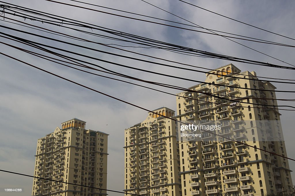 Residential buildings stand behind electrical cables in Gurgaon, India, on Wednesday, Nov. 21, 2012. Indian Prime Minister Manmohan Singh aims to spur spending on infrastructure to revive a faltering economy and tackle bottlenecks contributing to one of Asia's highest inflation rates. Photographer: Brent Lewin/Bloomberg via Getty Images