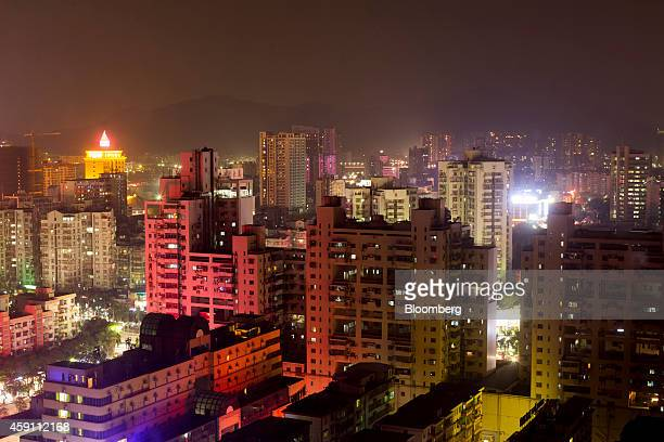 Residential buildings stand illuminated in the Gongbei district of Zhuhai Guangdong province China on Saturday Nov 15 2014 Investors piled into...
