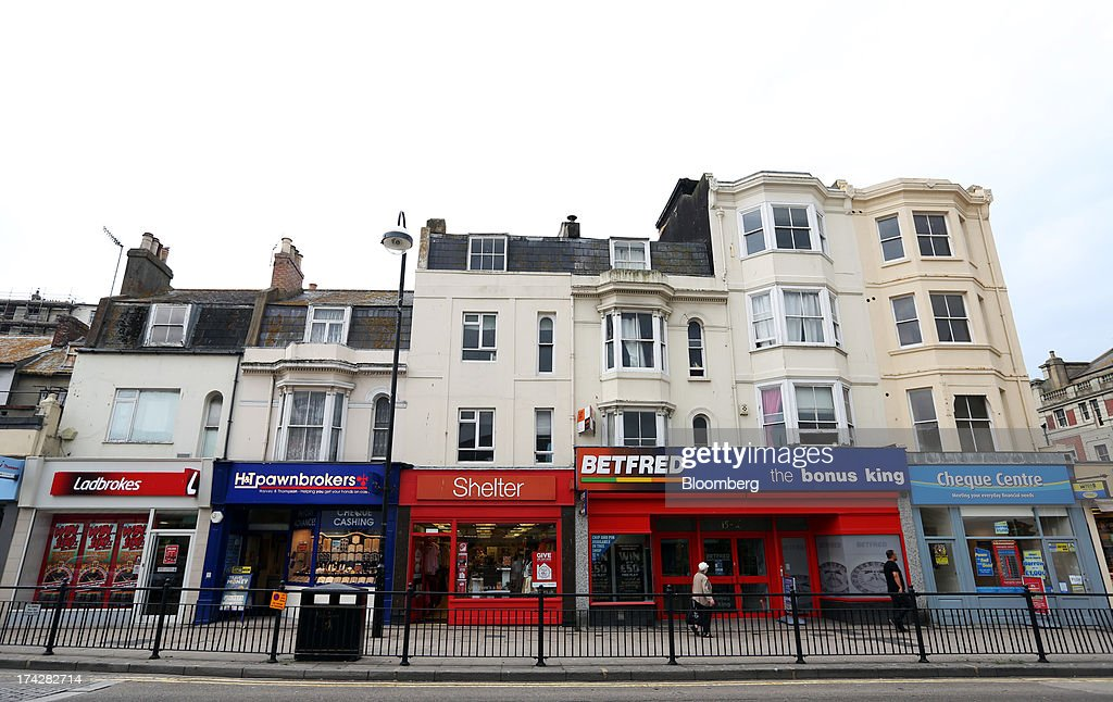 Residential housing sits above businesses premises, left to right, a Ladbrokes Plc bookmakers, a H&T Group Plc pawnbrokers, a charity store for Shelter, a Betfred Ltd. bookmakers and a payday loan store for Cheque Centre Ltd. in Hastings, U.K., on Tuesday, July 23, 2013. U.K. retail sales rose for a second month in June as discounts at department stores drove demand for clothes and electrical products. Photographer: Chris Ratcliffe/Bloomberg via Getty Images
