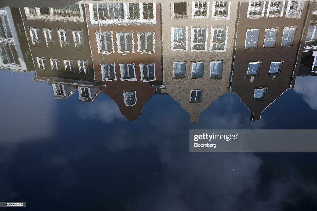 Residential property is seen reflected in the waters of a canal at Op Buuren, a housing development by the Vesteda Groep BV, in Maarsen, Netherlands, on Wednesday, July 16, 2014. Dutch home prices rose for a second quarter in the three months through June as consumers became more confident in the economic outlook, the Netherlands' real estate brokers association said. Photographer: Jasper Juinen/Bloomberg via Getty Images