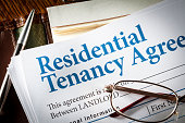 Residential Tenancy agreement with pen and glasses on desk