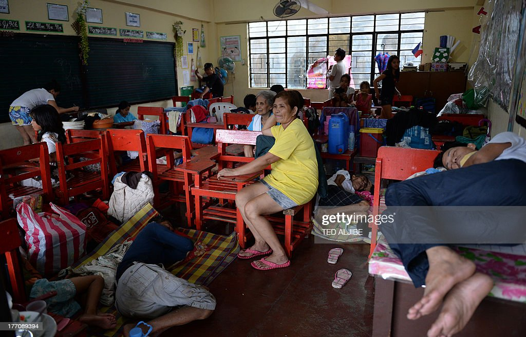 Residents affected by flooding due to heavy rains exacerbated by Tropical Storm Trami rest inside a classroom serving as a evacuation center in Marikina, east of Manila on August 21, 2013, as rains pounded the capital city for the third day. Heavy rain pounded the Philippine capital and surrounding areas for a third day August 21, adding to the misery of nearly 300,0000 exhausted people displaced from their flooded homes. AFP PHOTO / TED ALJIBE