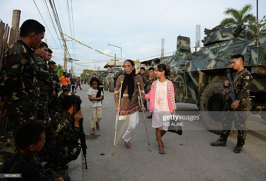 Residents affected by the standoff between Muslim gunmen and army troops walk past soldiers as they evacuate to a safer area in Zamboanga City on the...