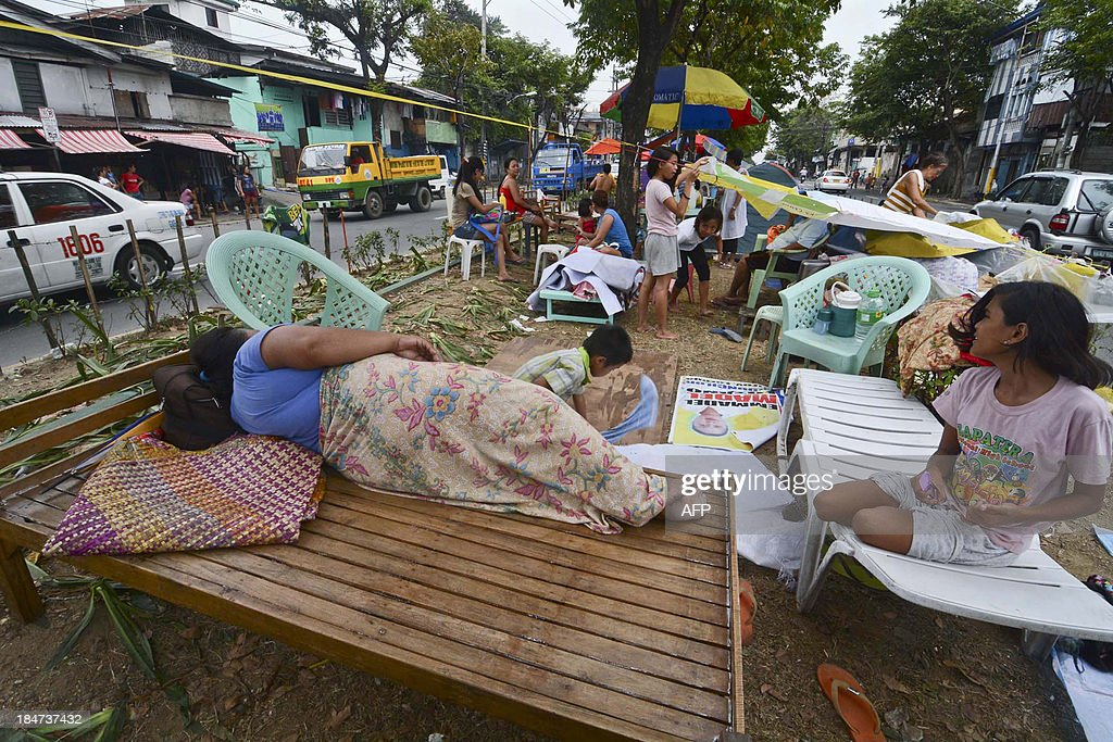 Residents afraid of aftershocks take shelter on a center island on a street in Cebu City in central Philippines on October 16 after experiencing...