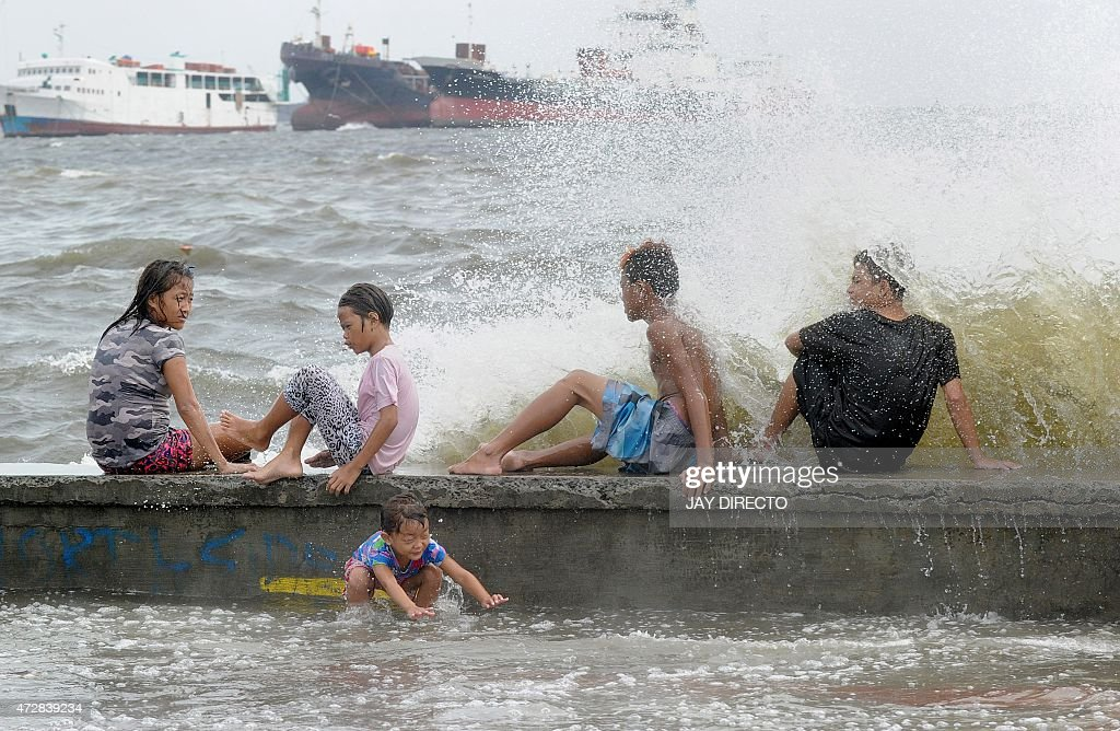 Residents along Manila Bay play in the waves created by nearby Typhoon Noul on May 10 2015 as it approaches the northern Philippines More than 2000...
