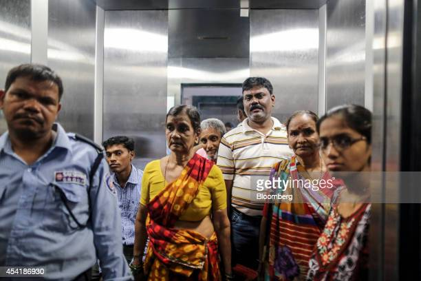 Residents and a security guard left stand in the elevator of a housing block developed by Omkar Realtors Developers Pvt in the Parel area of Mumbai...