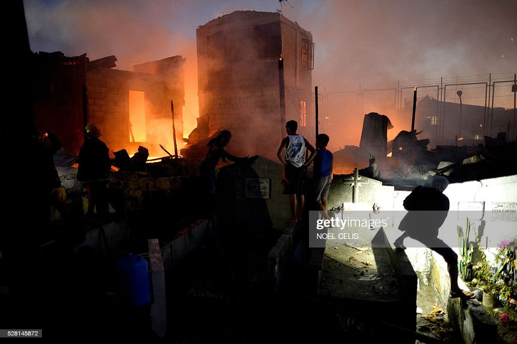 Residents and firefighters try to extinguish a fire that swept over a shanty community inside a public cemetery in Manila on May 4, 2016. No one was hurt in the fire, according to initial reports. / AFP / NOEL