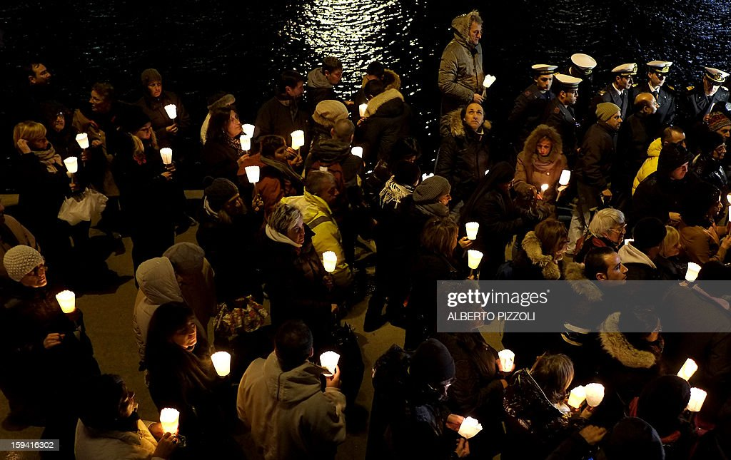 Residents and relatives hold candles as they take part in a vigil on January 13, 2013 on the Italian island of Giglio. Survivors, grieving relatives and locals on the island of Giglio gathered on January 13 to mark the first anniversary of the Costa Concordia cruise ship disaster, which claimed 32 victims.