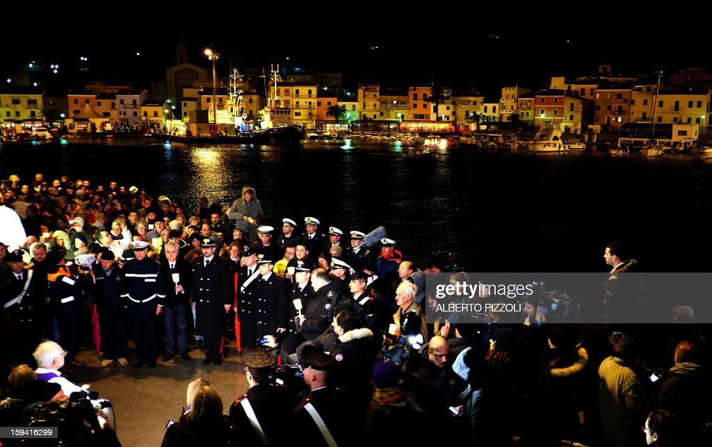 Residents and relatives take part in a vigil on January 13, 2013 on the Italian island of Giglio. Survivors, grieving relatives and locals on the island of Giglio gathered on January 13 to mark the first anniversary of the Costa Concordia cruise ship disaster, which claimed 32 victims. AFP PHOTO / ALBERTO PIZZOLI