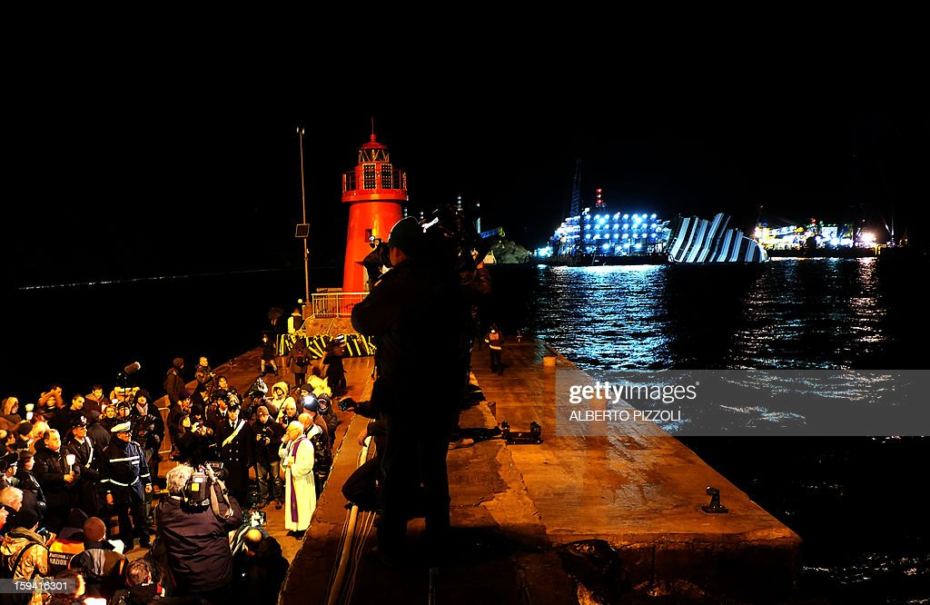 Residents and relatives take part in a vigil on January 13, 2013 on the Italian island of Giglio. Survivors, grieving relatives and locals on the island of Giglio gathered on January 13 to mark the first anniversary of the Costa Concordia cruise ship disaster, which claimed 32 victims.