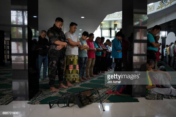 Residents and security personel attend Friday prayers inside a mosque in a cleared area inside the city a day before Ramadan on May 26 2017 in Marawi...