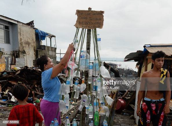 Residents and survivors of Super Typhoon Haiyan decorate a makeshift Christmas tree made up of plastic bottles and displayed along a street in the...
