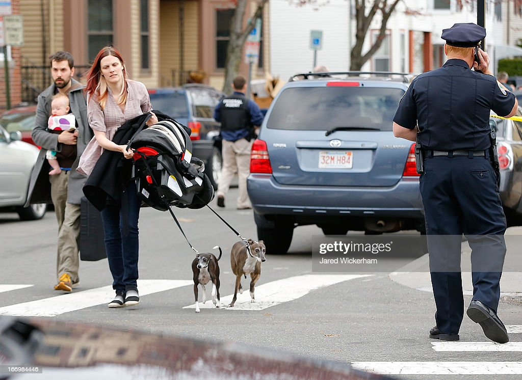 Residents and their pets are evacuated as members of the FBI, State Police, Boston Police, Cambridge Police, and other law enforcement agencies, survey the perimeter near the home of suspect #2 on Norfolk Street April 19, 2013 in Cambridge, Massachusetts. A Massachusetts Institute of Technology (MIT) campus police officer was shot and killed late Thursday night at the school's campus in Cambridge. A short time later, police reported exchanging gunfire with alleged carjackers in Watertown, a city near Cambridge. One suspect has been killed during the car chase and police are seeking another, believed to be the same person (known as Suspect Two) wanted in connection with the deadly bombing at the Boston Marathon earlier this week. Police have confirmed that the dead assailant is Suspect One from the recently released marathon bombing photographs.