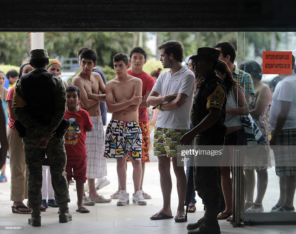 Residents and tourists queue to buy supplies outside a supermarket guarded by soldiers in Acapulco, state of Guerrero, Mexico, after heavy rains hit the area on September 17, 2013. Mexican officials launched an airlift to evacuate tens of thousands of tourists stranded in the flooded resort of Acapulco on Tuesday following a pair of deadly major storms. The official death toll rose to 47 after the tropical storms, Ingrid and Manuel, swarmed large swaths of the country during a three-day holiday weekend, sparking landslides and causing rivers to overflow in several states. AFP PHOTO/ Pedro Pardo