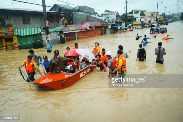 Residents are rescued by police and rescue volunteers after continued monsoon rains triggered by tropical storm FungWong have inundated parts of...